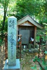 この墓碑は、半円柱型のキリシタン墓碑で、墓石の上部、本来なら伏碑にした場合、正面にあたるところに、「台付干十字紋」を刻んだ典型的なキリシタン墓碑です。現在は正面を向いている、かつての墓碑の底面には「天正四年丙子十一月十一日/不染院水心日栄霊/一瀬治部太輔」と刻んであります。ここから、墓の主は、日本初のキリシタン大名大村純忠とともに横瀬浦で洗礼を受けた一瀬栄正と考えられてきました。  ところが、近年の調査で「干十字紋」の横に「慶長十九年」(1614年)の文字が発見されたことから、この墓は、慶長19年に一瀬栄正ではない別のキリシタンのために建てられたと考えられます。  その後、キリシタン禁教時代となり、大村藩内ではキリシタン墓地の探索と破壊が行われ、取り締まりが厳しくなったため、墓碑を縦に起こし、仏教の戒名を記し、仏式墓碑に改造したものと考えられています。墓の右には手水鉢が置かれていますが、これも元は同様のキリシタン墓碑であったものを転用したものです。